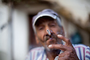 Portrait of a man with cigarette living in the Roma part of the city of Crnik, Macedonia.