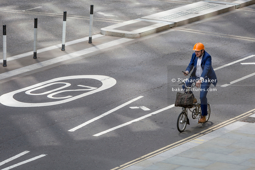 A cyclist checks messages or map on London Wall, the site of the original Roman walled boundary of their Londinium settlement - now known as the City of London, the capital's financial district, on 21st August 2018, in London, England.