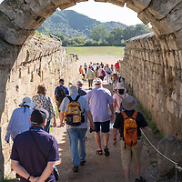 Lindblad Expeditions guests walk through the archway into the ancient Olympic stadium. The UNESCO World Heritage Site of Ancient Olympia is a site on Greece's Peloponnese peninsula that hosted the original Olympic Games, founded in the 8th century B.C. Its extensive ruins include athletic training areas, a stadium, and temples dedicated to the gods Hera and Zeus.