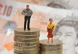 File photo dated 27/01/15 of plastic models of a man and woman standing on a pile of coins and bank notes. Men are significantly more likely than women to try to evade paying tax, researchers say.