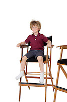 School kid sitting on director's chair over white background