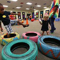 Caleb Williams, 3, steps from one tire to the other as he goes through the obstacle course in the Zoom Room during Fun and Fit Friday at HealthWorks. The camp is for children and their adult relatives where they have story time, crafts and an obstacle course in the Zoom Room.