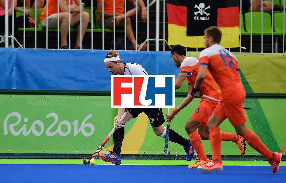 Germany's Moritz Trompertz (L) vies with Netherlands' Glenn Schuurman (C) and Netherlands' Sander De Wijn during the mens's field hockey Germany vs Netherlands match of the Rio 2016 Olympics Games at the Olympic Hockey Centre in Rio de Janeiro on August, 12 2016. / AFP / MANAN VATSYAYANA        (Photo credit should read MANAN VATSYAYANA/AFP/Getty Images)