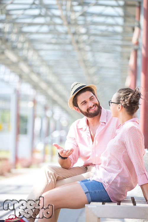 Happy man talking to woman while sitting on bench under shade