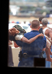 01 Sept, 2005. New Orleans, Louisiana.<br /> Mass evacuation of New Orleans begins. People collapse in the heat as massed crowds attempt to board busses out of New Orleans. A State Trooper advised that the individual in the photograph passed away. We were unable to verify this.<br /> Photo©; Charlie Varley/varleypix.com