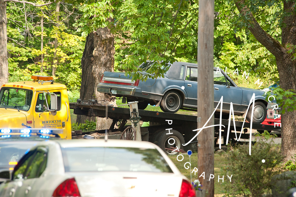 A wrecker removes a vehicle, believed to be owned by the suspect in a Laconia shooting,  from a residence on Brown Hill Road in Belmont on Wednesday, August 4, 2010.  {Alan MacRae/for the Citizen)