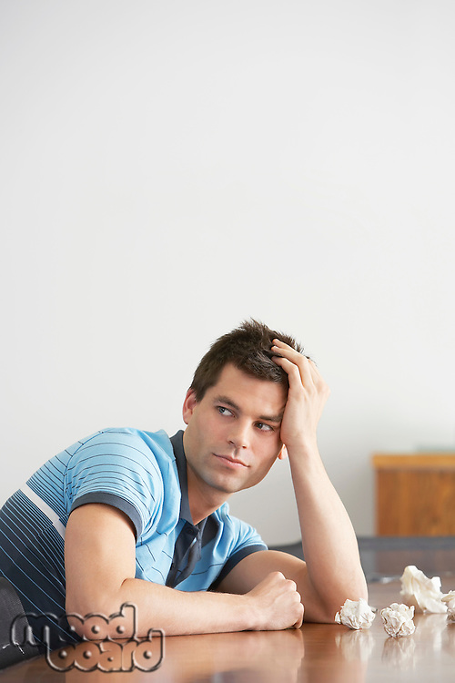 Frustrated Man sitting at conference table With Crumpled Paper looking over shoulder side view