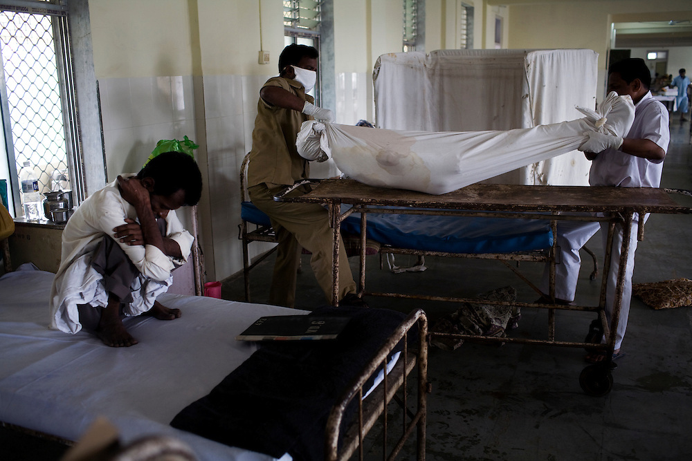 Orderlies at the Group of TB Hospitals in Mumbai remove a recently deceased patient as another patient sits on his bed.