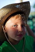 Stock photography of a kid in a cowboy hat at the Fort Worth Stock Yards sign in Fort Worth, Texas.
