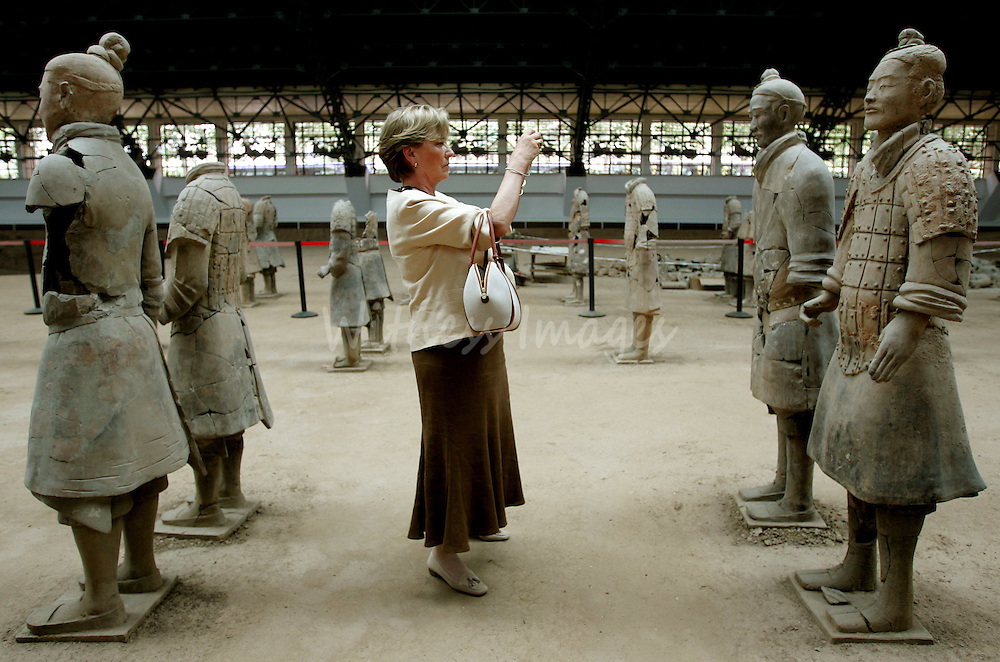 Belgium's Queen Paola takes a picture of life-sized sculptures of warriors during her visit to the famous excavation site of the Terracotta Warriors in Xian, China, June 8, 2005. King Albert and Queen Paola are on an eight-day state visit to China. REUTERS/Thierry Roge  THR