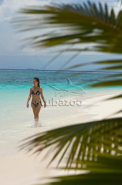 Woman walking along beach, Pom Pom Island Resort, Celebes Sea, Sabah, East Malaysia.