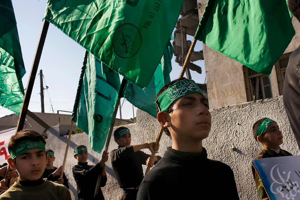"Palestinian boys carry HAMAS banners during a ""Victory"" parade thrown by militant Palestinian political group HAMAS January 20, 2009 in Gaza City. Several thousand marchers celebrated what HAMAS called the defeat of Israel during the recent 21 day offensive by Israeli forces against HAMAS fighters. During the operation more than 1500 Palestinians were killed and more than 4000 homes destroyed in the narrow Gaza Strip..."