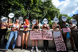 © Licensed to London News Pictures. 19/09/2012. London,UK. SlutWalk Activists dressed in underwear with slogans on their bodies demonstrate outside Downing Street, London against police and court treatment of rape victims, on September 19, 2012 .Photo credit : Thomas Campean/LNP...