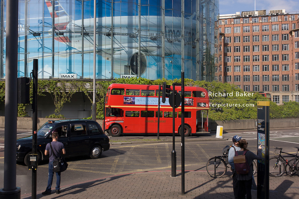 A red routemaster bus drives beneath a large advert for American Airlines of a wide-bodied airliner in Waterloo, south London.