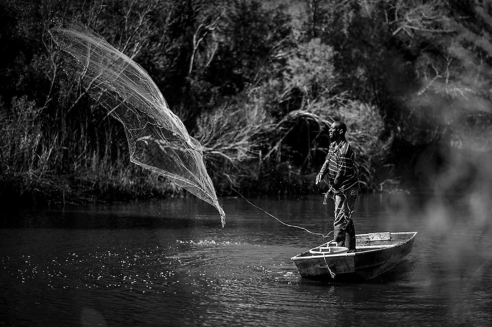 A Gullah man throws his cast net for shrimp and mullet from his boat on one of the saltwater creeks on St. Helena Island, S.C. St. Helena has been able to stave off rampant development and as a result, many of the traditional fishing grounds are still accessible.