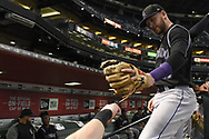 PHOENIX, AZ - SEPTEMBER 14:  Trevor Story #27 of the Colorado Rockies fist bumps a teammate while entering the dugout for the MLB game against the Arizona Diamondbacks at Chase Field on September 14, 2017 in Phoenix, Arizona.  (Photo by Jennifer Stewart/Getty Images)