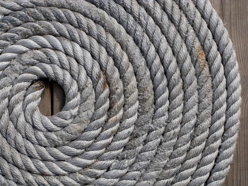 A coil of rope waits on a dock in Kladeshölmen, Sweden.