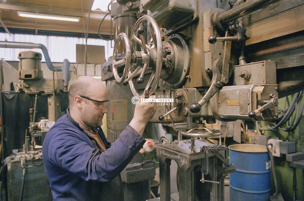 Radio drill operator at work using drilling machine at engineering works,