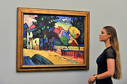 "© Licensed to London News Pictures. 15/06/2017. London, UK. A staff member views ""Murnau - Landschaft mit grünem Haus"", 1909, by Wassily Kandinsky (estimate GBP15-25m).  Preview of Impressionist and Modern art sale, which will take place at Sotheby's New Bond Street on 21 June.  Photo credit : Stephen Chung/LNP"
