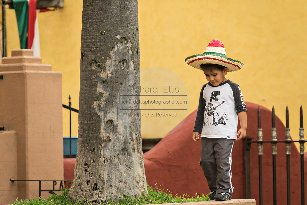 A young Mexican boy wearing a straw sombrero plays in the Jardin Allende during the week long fiesta of the patron saint Saint Michael September 26, 2017 in San Miguel de Allende, Mexico.