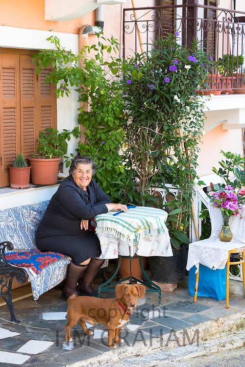 Old Corfiot woman wearing traditional black clothes at home with her dachshund dog in Doukadis, Corfu, , Greece