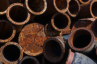 Stack of rusting drainage pipes used for tidal sediment diversion with strong color and graphical quality. Wanzhou, Zhejang, China.