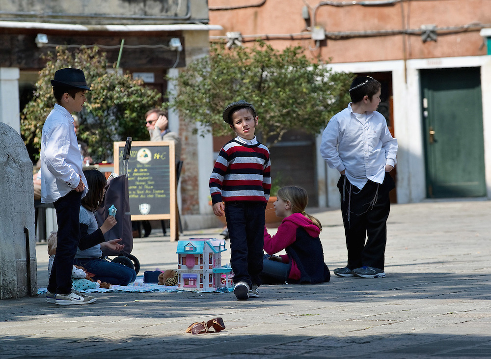VENICE, ITALY - NOVEMBER 15:  Children from the Jewish community play in the main campo of the Ghetto on November 15, 2011 in Venice, Italy. Established in 1516 the Ghetto of Venice was the area were Jews were compelled to live during the Venetian Republic. The English term 'ghetto' is derived from the Venetian term for 'slag' and refers to the refuse left the foundry that was located on the same island. In present times the ghetto is a multi-ethnical area area seen as the cultural heart of the city, but with five synagogues remains the centre of the of Jewish community.