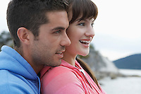 Couple embracing at ocean smiling close-up