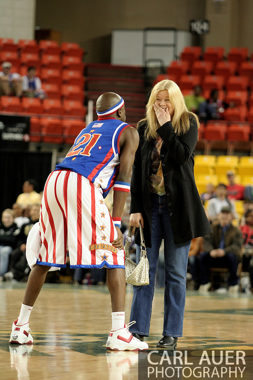 """04 May 2006: Kevin """"Special K"""" Daley pleads for a kiss from Rene Legruc of Anchorage after stealing her purse during the Harlem Globetrotters vs the New York Nationals at the Sulivan Arena in Anchorage Alaska during their 80th Anniversary World Tour.  This is the first time in 10 years that the Trotters have visited Alaska."""