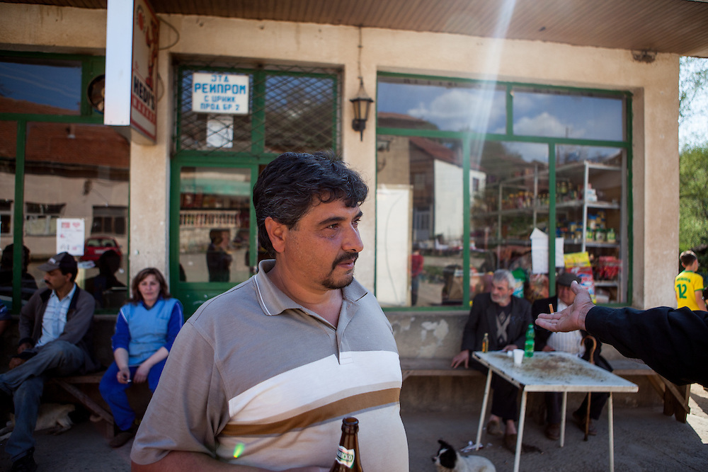 A group of men and the shop assistant sitting and talking in front of the local grocery store in the city of Crnik. Crnik has almost 90% of unemployment.