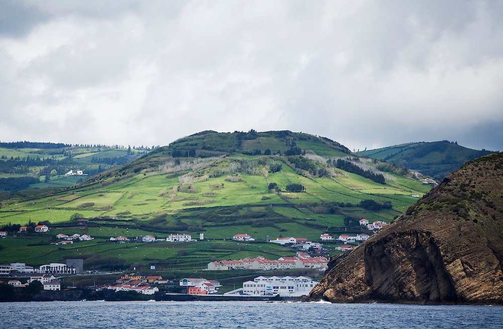 The headland of Porto Pim upon approaching Faial from the ocean. This is the rock where the iconic photograph of a gigantic wave dashing the rock face and resembling the face of Neptune was taken. The Azores are a group of islands under Portuguese sovereignty. They Mark the most westerly point of the E.U. and earn most of their income from agriculture and tourism.