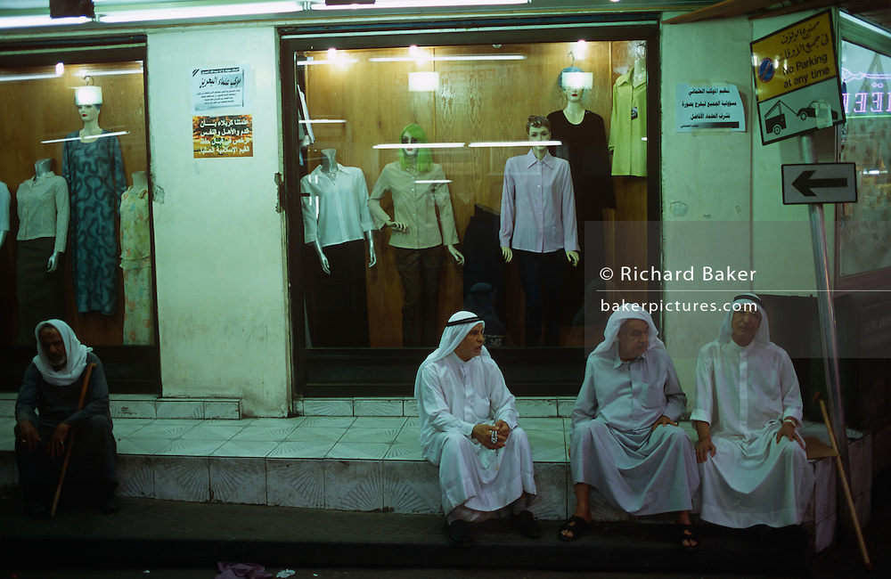 Middle-aged men sit chatting on a Manama City street pavement behind a womens' clothing outfitters in Bahrain, Gulf State