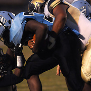 South Brunswick High School's Damani Johnson is tackled by North Brunswick High School's DeShawn Montgomery left, and KJ Bowden Friday September 13, 2013 at Sough Brunswick High School. (Jason A. Frizzelle)
