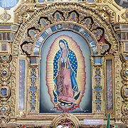 An ornately decorated altar with extensive gold lining depicting Our Lady of Guadalupe in the Iglesia de San Francisco (Church of San Francis). The church is most well known as the resting place and tomb of Santo Hermano Pedro de San Jose de Bethancourt (Saint Herman Pedro of Stain Joseph of Bethancourt), a locally revered figure from the 16th century who build a local hospital for the poor, amongst other things.