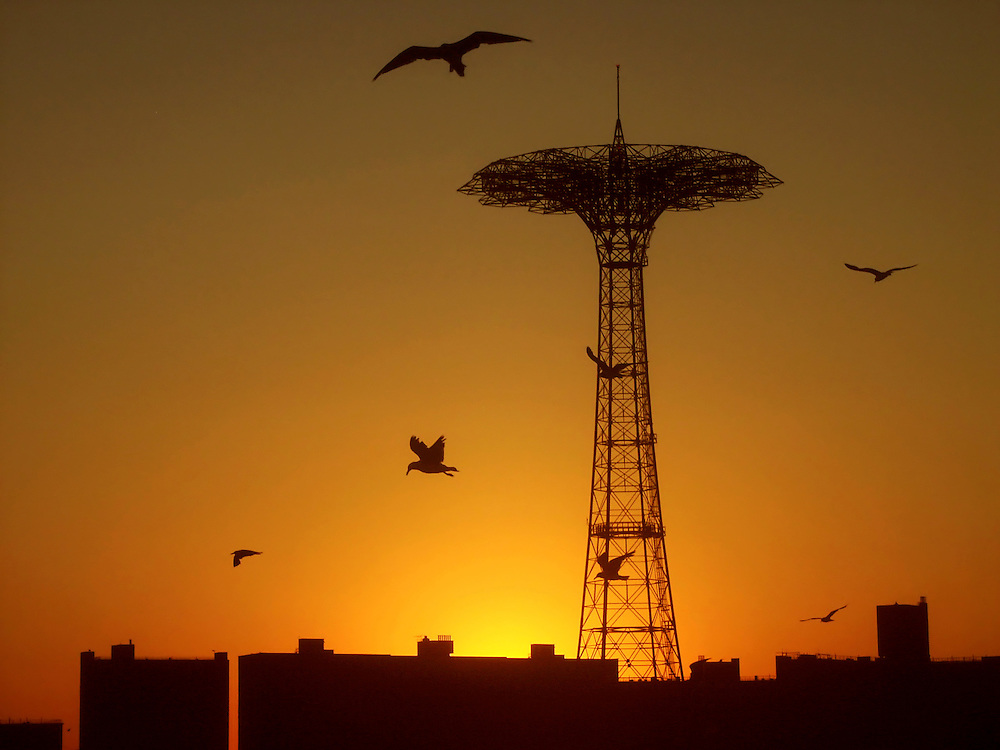 The sun sets behind the old Parachute Jump.