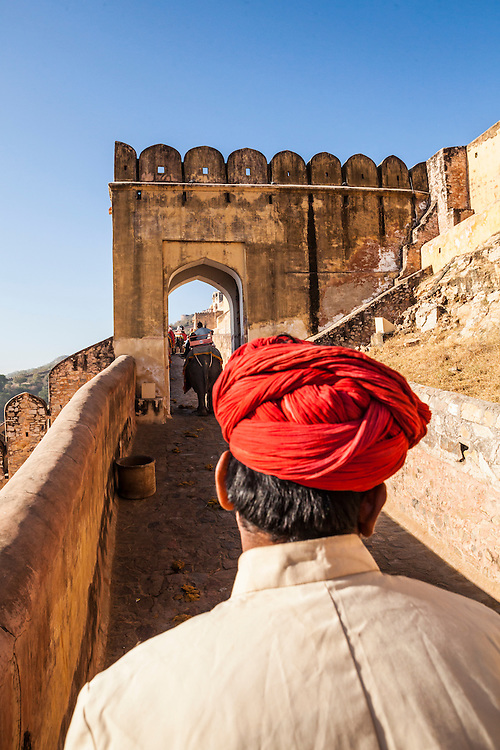 A view from atop an elephant looking at the back of the elephant drivers head as they go up the ramps to Amer Palace, Amer, Rajasthan, India.