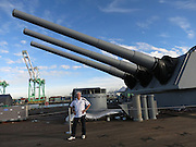 Paul Spinelli poses for a photo points in the direction of her huge guns as the USS Iowa battleship sits docked as a museum and tourist attraction in the San Pedro Harbor on November 30, 2013 in Los Angeles, California. ©Wayne Koch