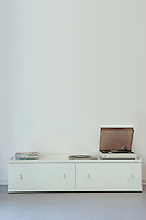 Record player on cabinet against wall