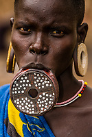 Mursi tribe woman with clay lip plate and headdress, Mago National Park, Lower Omo Valley, Ethiopia.