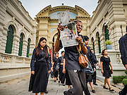 29 OCTOBER 2016 - BANGKOK, THAILAND:  A man holds a picture of the Bhumibol Adulyadej, the King of Thailand, while he walks into the Grand Palace to homage to the King. Saturday was the first day Thais could pay homage to the funeral urn of the late Bhumibol Adulyadej, King of Thailand, at Dusit Maha Prasart Throne Hall in the Grand Palace. The Palace said 10,000 people per day would be issued free tickerts to enter the Throne Hall but by late Saturday morning more than 100,000 people were in line and the palace scrapped plans to require mourners to get the free tickets. Traditionally, Thai Kings lay in state in their urns, but King Bhumibol Adulyadej is breaking with tradition. His urn reportedly contains some of his hair, but the King is in a coffin,  not in the urn. The laying in state will continue until at least January 2017 but may be extended.      PHOTO BY JACK KURTZ