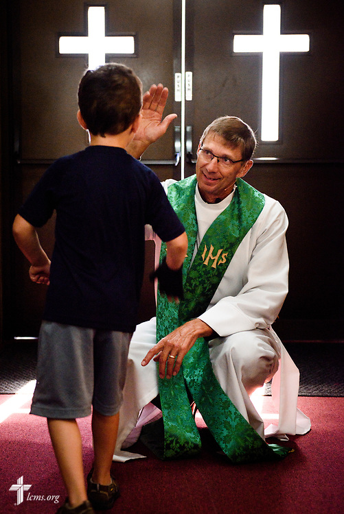 The Rev. Steven Struecker, full-time farmer and pastor of Zion Evangelical Lutheran Church, Lu Verne, Iowa, and Immanuel Lutheran Church, Livermore, Iowa,  Zion greets a young church member before worship at Zion on Sunday, July 9, 2017. LCMS Communications/Erik M. Lunsford