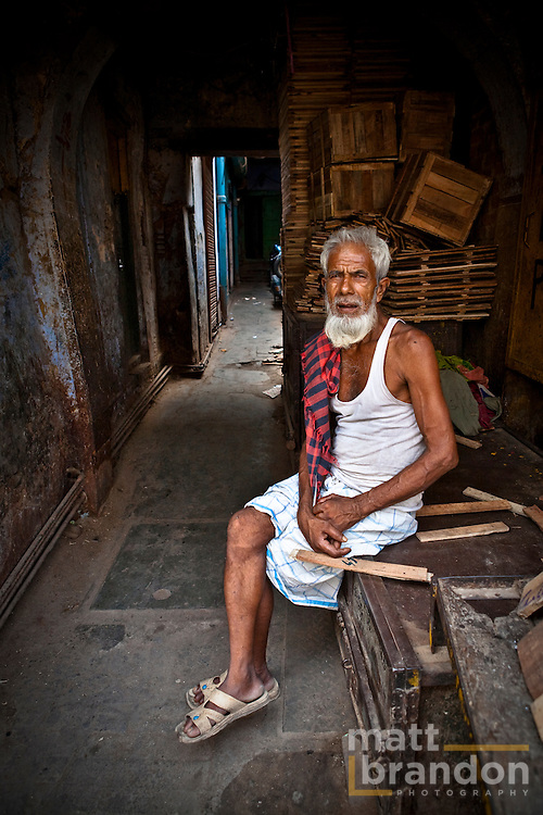 A man sits next to his shop where he makes wooden crates.