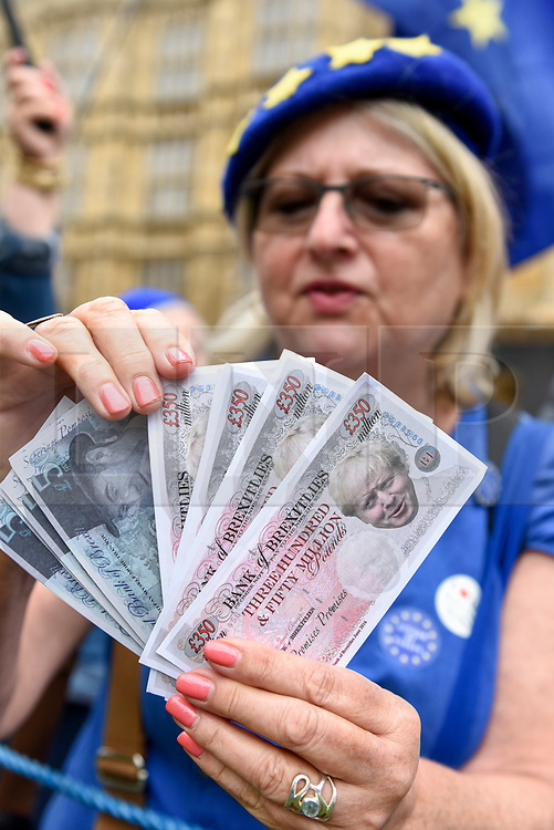 © Licensed to London News Pictures. 12/06/2018. LONDON, UK.  An anti-Brexit protester poses with fake money during a demonstration outside the Houses of Parliament as MPs begin two days of debate and vote on amendments to the EU Withdrawal Bill.  Photo credit: Stephen Chung/LNP