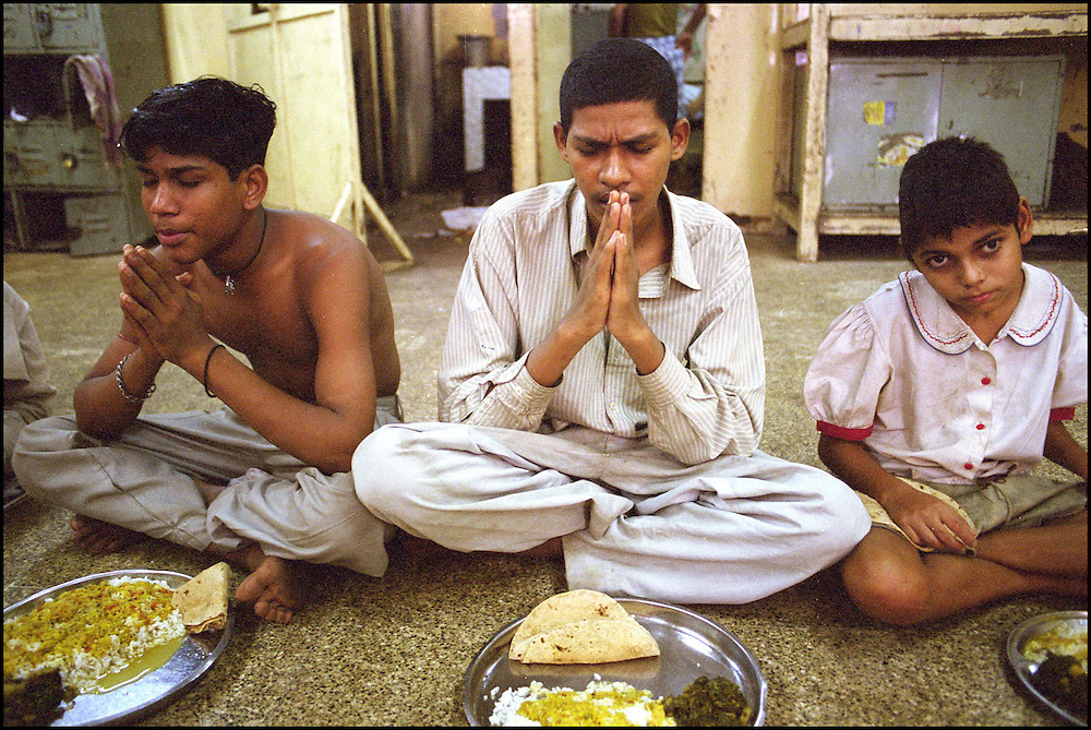 INDIA. Mumbai (Bombay). 2002. Two homeless youths pray before starting their meal while a mentally disabled boy (right) stares into the camera. Children who are staying at the shelter receive two meals a day provided by a local NGO.