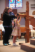 Patricia Hirthe venerates a cross at St. Patrick Church in Menasha, Wis., on Good Friday with her children. (Sam Lucero photo)