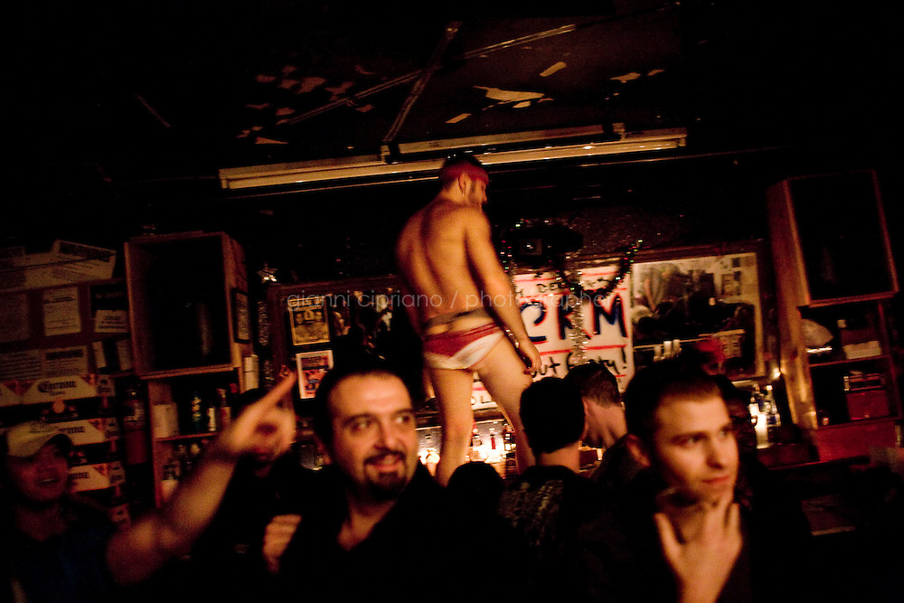 """11 December, 2008. New York, NY. Daniel Alexander Osach (or Dan Alex), 24, dances on the bar of The Cock Bar while the audience pays attention to the """"Horny Reindeers"""", half-naked men perform who perform a burlesque show on stage. Daniel Osach is a gay Go-Go dancer who grew up in New Haven, CT, and moved to New York a year ago. During the day he works for Christopher Hyland, Inc., a high-end fabrics purveyor. At night, he works as a Go-Go dancer in gay and women clubs around New York City. """"My life is work, gym, dance and sleep"""", Daniela says. Dan has a bachelor in English and majored in Poetry and Economics. After graduation in 2006 he worked as a store manager in a mall for 4 months in Connecticut. Tired and depressed of his job, he went to Florida to relax and then came to New York a year ago. He usually dances at """"The Cock"""", a  East Village gay bar. """"The Cock is not an institution. It's a landmark"""" Daniel says. Daniel aspires to become maybe a teacher or to work for a travel magazine. """"What I would really love to do is to live my life laying down at the beach and reading poetry""""<br /> <br /> ©2008 Gianni Cipriano for The New York Times<br /> cell. +1 646 465 2168 (USA)<br /> cell. +1 328 567 7923 (Italy)<br /> gianni@giannicipriano.com<br /> www.giannicipriano.com"""