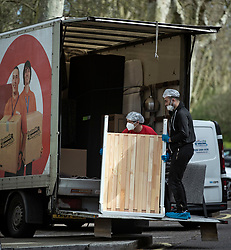 © Licensed to London News Pictures. 29/03/2020. London, UK. Workers from a removals company wearing protective clothing and medial face masks while moving belongings form a property in Maida Vale, LondonA , during lockdown to slow the spread of COVID-19. Members of the public have been told they can only leave their homes to exercise briefly once a day, and to go to shops for essentials when absolutely necessary, in an attempt to fight the spread of COVID-19. Photo credit: Ben Cawthra/LNP