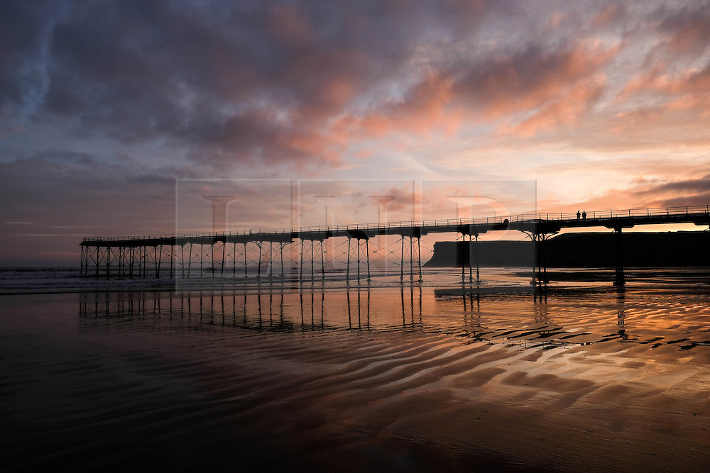 © Licensed to London News Pictures. <br /> 30/10/2016. <br /> Saltburn-by-the-Sea, UK.  <br /> A couple stand on the pier watching the sun rise over Saltburn-by-the-Sea on the north east coast of England.<br /> Photo credit: Ian Forsyth/LNP