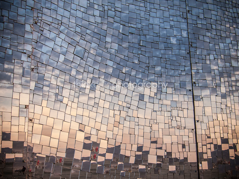Abstract refection of sunrise in wavy, mirrored mosaic wall, Burning Man, 2009.