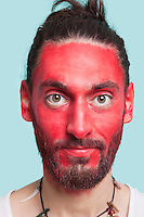 Portrait of young man with red painted face against blue background